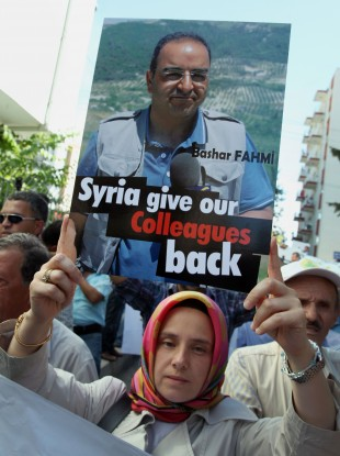 Arzu Kadumi, wife of journalist Bashar Fahmi, captured by Syrian forces, joins some 200 Turkish journalists marching to the Syrian embassy in Ankara, Turkey, Friday, Aug. 31, 2012