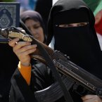 8 June 8: A Syrian woman holds an AK-47 during an anti-Bashar Assad protest after Friday prayers on the outskirts of Idlib, Syria. (AP Photo/Khalil Hamra, File)