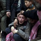 8 March: Ahmed, centre, mourns his father Abdulaziz Abu Ahmed Khrer, who was killed by a Syrian Army sniper. (AP Photo/Rodrigo Abd, File)