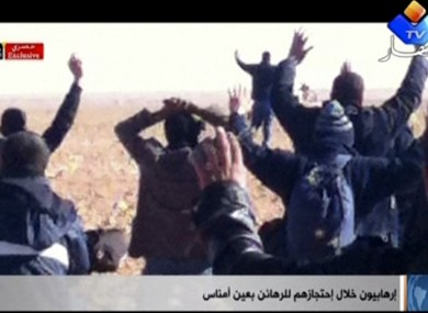 In this image made from video, a group of people believed to be hostages kneel in the sand with their hands in the air at an unknown location in Algeria.