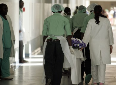 File image of hospital hospital staff pushing trolley's carrying bodies of people trampled to death in a stampede at another event at Luanda stadium.