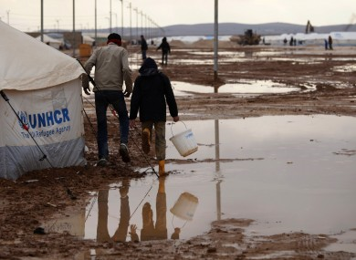 Syrian refugees walk on water and mud, at Zaatari Syrian refugee camp, near the Syrian border in Mafraq, Jordan.