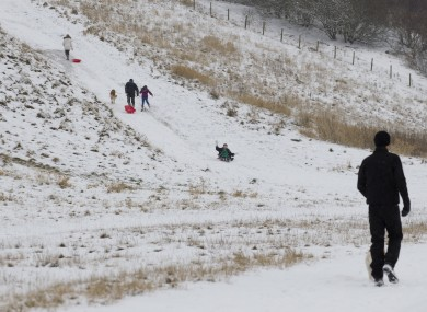 Children play in the snow in Cheshire, England. Four people were killed in an avalanche in Scotland yesterday.