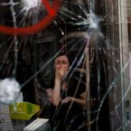 Mireia Arnau, 39, reacts behind the broken glass of her shop, stormed by demonstrators during clashes with the police at a general strike in the city. (Image: Emilio Morenatti)