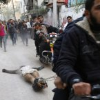 Palestinian gunmen ride motorcycles dragging the body of a man who was killed earlier as a suspected collaborator with Israel. (Image: Adel Hana)