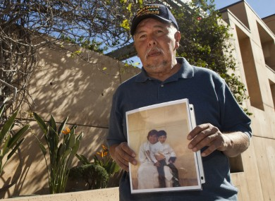 Frank Zamora, 67, holds an old photo of his son Dominic Zamora, then 8, sitting on the lap of his abuser, priest Michael Stephen Baker.