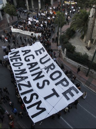 Protesters hold a giant banner during a silent march through the streets of Athens in protest against racism and neo-nazism.