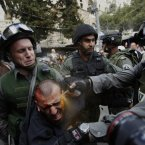Israeli border officers pepper spray an injured Palestinian protester during clashes on Land Day outside Damascus Gate in Jerusalem's Old City on 30 March last year. (Image: Ammar Awad)