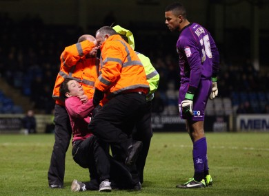 The fan is tackled by stewards as Wycombe goalkeeper Jordan Archer watches on.