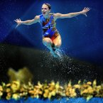 A swimmer soars above the water in the London 2012 synchronized swimming competition. (Image: Wei Zheng)