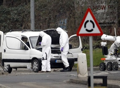 Police forensic officers examine a car in which four mortar rounds were found in Derry today
