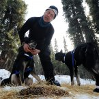 Four-time champion Martin Buser booties up his dog team.