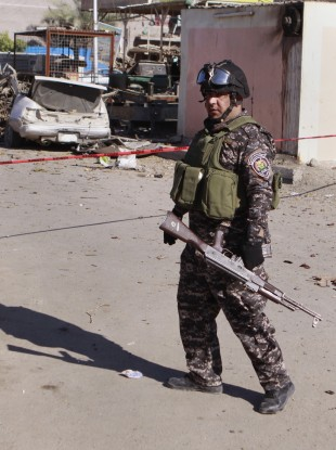 A police man stands guard at the scene of a car bomb attack in the Shiite stronghold of Sadr City, Baghdad